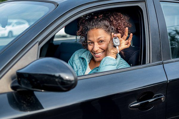 女人微笑着展示新的汽车钥匙和汽车-芝加哥,伊利诺斯州保险中心