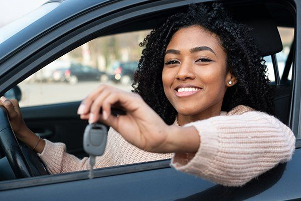 快乐的年轻女子坐在她的新车-芝加哥,伊利诺斯州保险中心公司