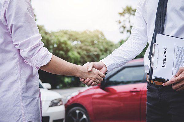 保险代理人和客户在索赔后握手-芝加哥,伊利诺斯州保险中心公司