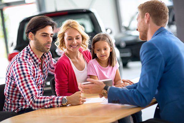 微笑的年轻家庭与汽车经销商-芝加哥,伊利诺伊州保险中心公司