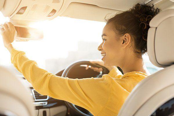 快乐女孩触摸后视镜,而驾驶汽车-芝加哥,伊利诺伊州保险中心公司