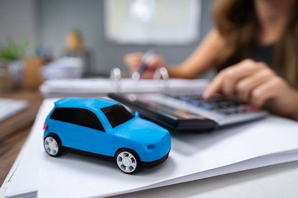 在计算贷款的女商人前面的蓝色汽车-芝加哥,伊利诺斯州保险中心