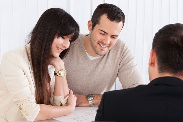 Young couple discussing with consultant in office