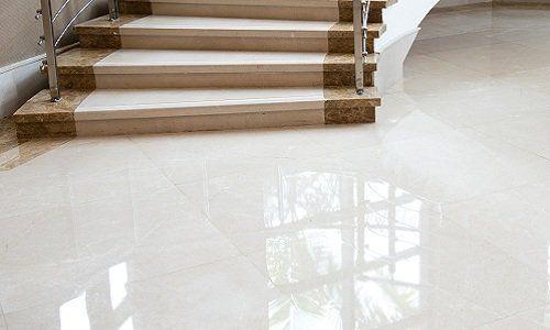 Suolo di marmo bianco e una scala di cui vediamo i primi scatti realizzati in marmo di due colori