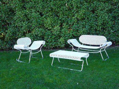 un giardino con un divano, poltrona e un tavolino in ferro