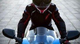 Giovane con equipaggiamento di sicurezza e casco in una moto blu