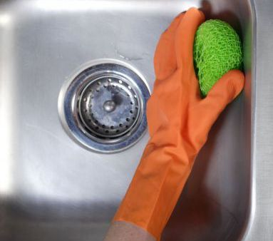 Someone from our commercial cleaning team scrubbing a steel sink in Honolulu, HI