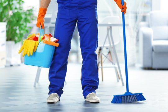 Un addetto alla pulizia con prodotti per l'igiene della casa a Milano