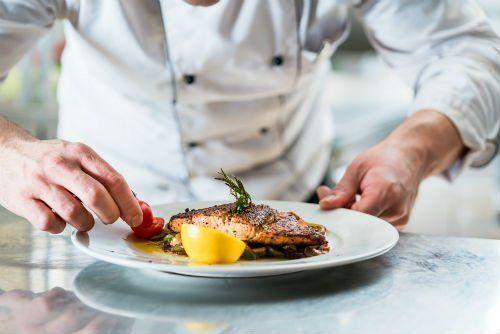 un cuoco mentre impiatta un filetto di pesce con pomodorini e limone