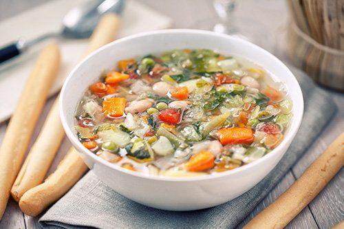 Un piatto di minestrone con grissini