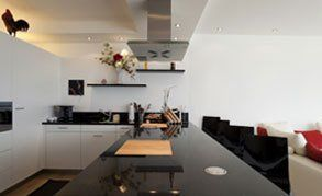 A large black and white kitchen with glossy black worktops