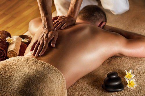 Uomo sdraiato al quale fanno un massaggio alla schiena
