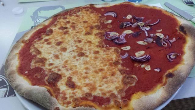 Mezza pizza di pomodori e formaggio e mezza di cipolla e aglio