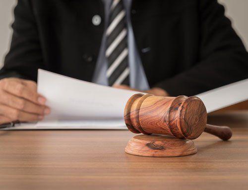 un uomo in giacca e cravatta seduto alla scrivania mentre esamina in fascicolo e accanto un martello delle udienze di legno