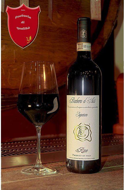 Bottiglia di Barbera d'Asti vicino a un bicchiere di vino