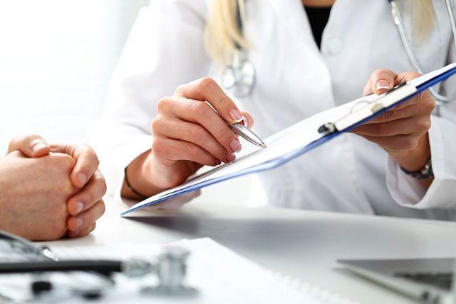 una dottoressa con un rilievo di scrittura in mano e una penna