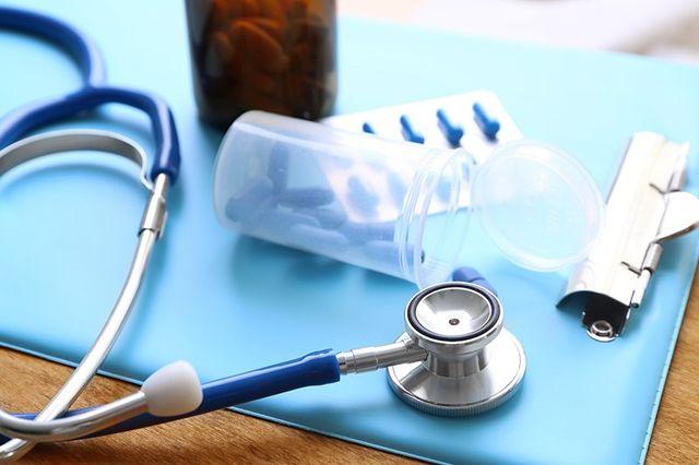 uno stetoscopio, un flacone di pillole e un blister su un tavolo