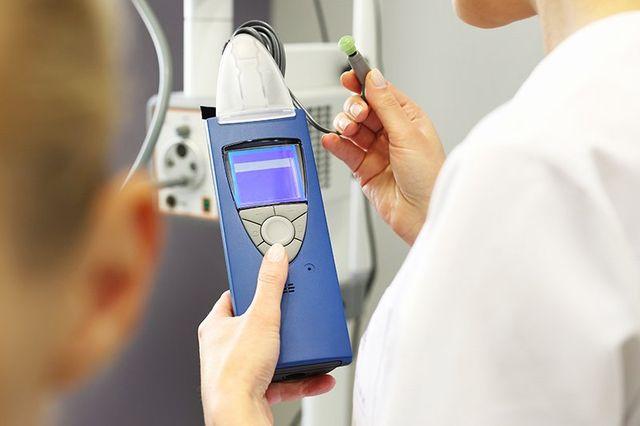una mano di una dottoressa con un apparecchio elettromedicale