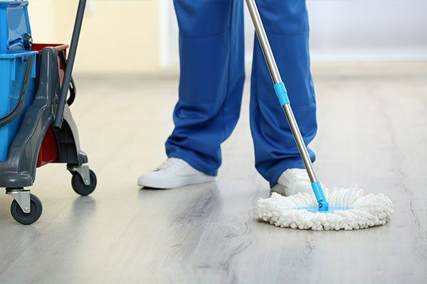 un inserviente con un mocio mentre pulisce il pavimento