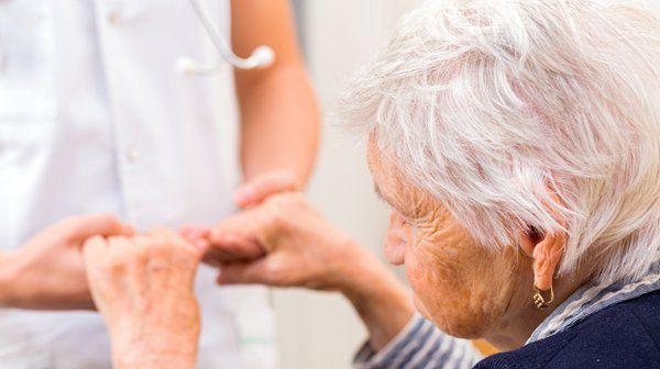 Giovane dottoressa tiene le mani di un'anziana a Messina
