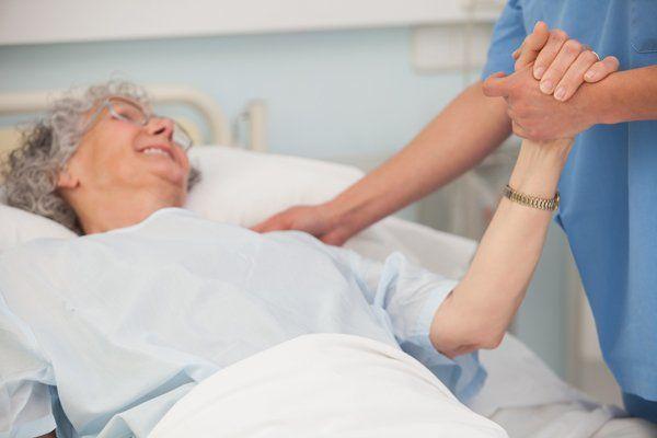Assistente teiene la mano di un'anziana a Messina