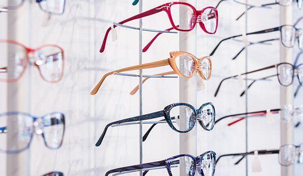 degli occhiali da vista di diversi colori visti lateralmente esposti su dei pannelli al muro