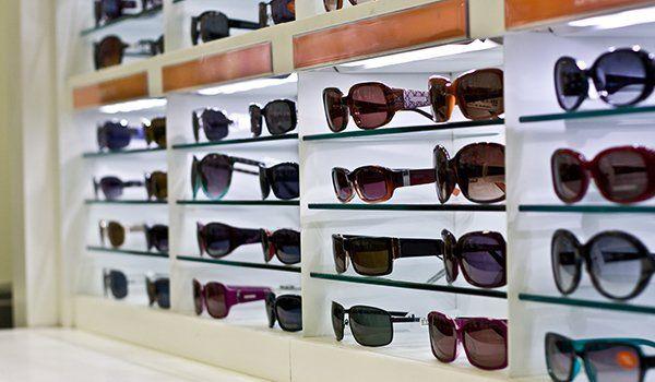degli occhiali da sole di diversi colori esposti su dentro a degli scompartimenti a muro