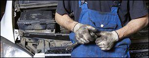 meccanico con tuta da lavoro sistema un pezzo meccanico per un auto