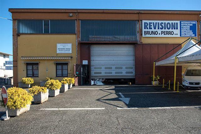 esterno del Centro revisioni Bruno e Perro con vista del parcheggio con dei vasi con delle piante e sulla destra un bersò con una tenda bianca con sotto un furgone parcheggiato