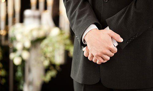 Una persona con le mani giunte durante un funerale