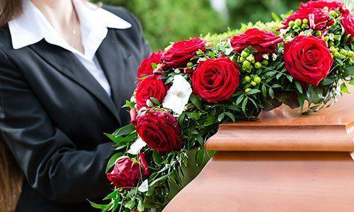 Donna in lutto a un funerale con di fronte delle rose rosse su una bara