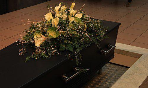 Cofanetto in legno con fiori funebri, cerimonia di cremazione