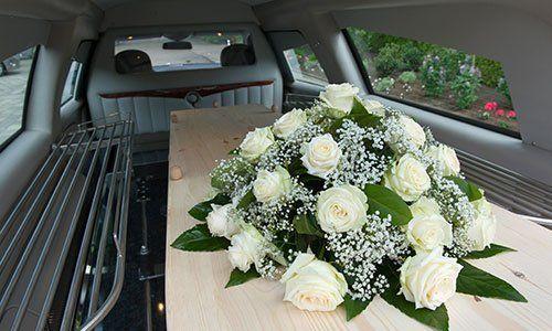 Una bara in una macchina di lutto con un arrangiamento di fiori