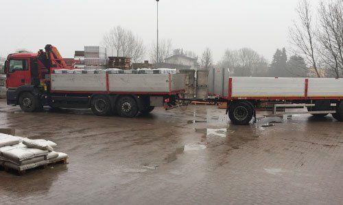 due camion di color rosso con il rimorchio grigio in un parcheggio di una ditta