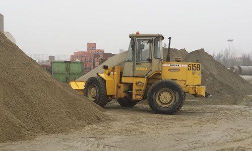una scavatrice gialla al lavoro affianco a una pila di terra