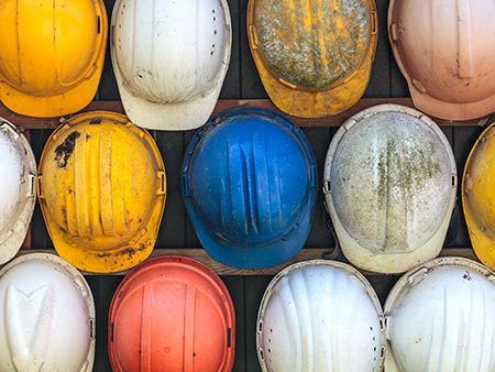 Close up of various construction hard hats in rows