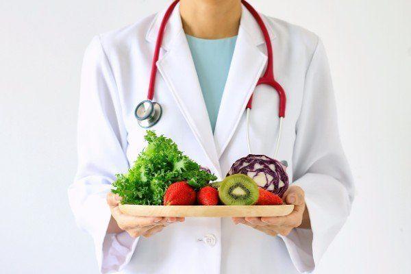donna con camice bianco e in mano un vassoio con frutta e verdura