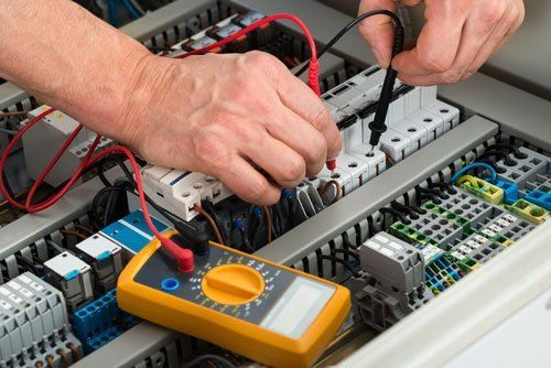 Close up of a male electrician checking fuse with multimeter