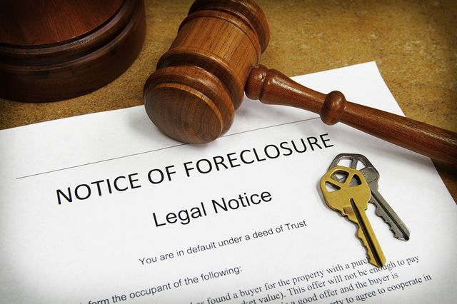 Foreclosure document with house keys and gavel