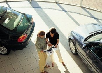 una donna e un uomo che guardano un depliant delle macchine in uno showroom