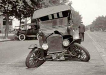 foto in bianco e nero di una vecchia macchina antica con l'asse delle ruote danneggiato