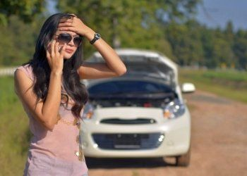 una ragazza al telefono con la macchina in panne
