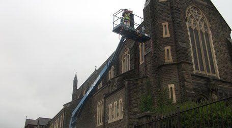 A cherry picker being used to carry out repairs on a church