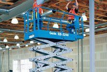 Two men working on a scissor lift