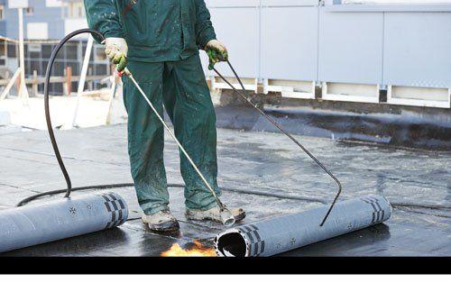 Operaio impermeabilizza un tetto