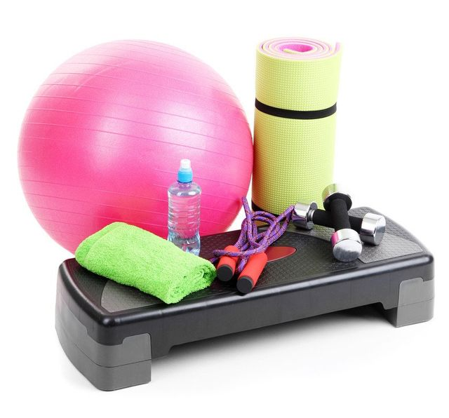 An exercise step, fitness ball, skipping rope, weights, a bottle of water and a rolled-up mat