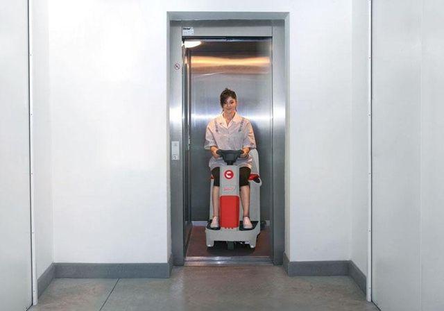 una donna seduta su una lavasciuga in un ascensore