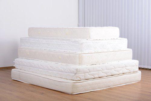 pila di materassi di colore bianco e avorio all'interno di una stanza con parquet