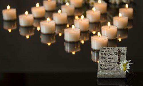 Un insieme di lumini bianchi accesi su uno sfondo nero e davanti una cornice con scritte in latino e un crocefisso
