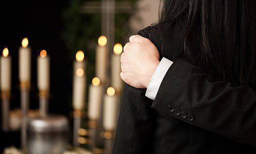 Vista di un uomo sulle spalle di una donna che indossa una giacca nera e davanti delle candele accese